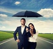 Couple under black umbrella at outdoor. Happy smiley couple under black umbrella at outdoor Stock Photos