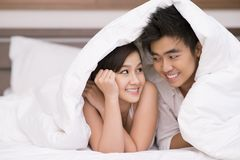 Couple under blanket. Portrait of young Asian couple looking at one another with smiles under blanket Royalty Free Stock Images