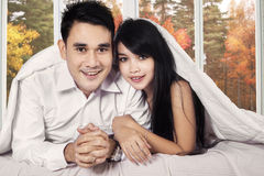 Couple under blanket looking at camera Stock Images