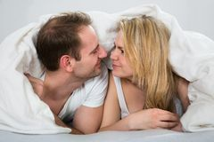 Couple under blanket looking at each other Stock Photography