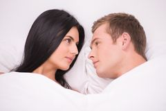 Couple is under blanket looking at each other Stock Photo
