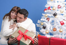 Couple under christmas tree. Mid adult romantic couple on christmas tree with presents stock photos