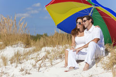 Couple Under Colorful Umbrella on Beach Royalty Free Stock Photography