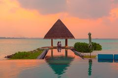 Couple Under Hut Beside Sea and Infinity Pool stock photography