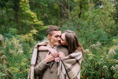 Couple under the plaid in an autumn romantic forest. Autumn wedding outdoors. Stock Photo