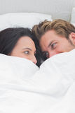 Couple under the quilt looking at each other Royalty Free Stock Photography