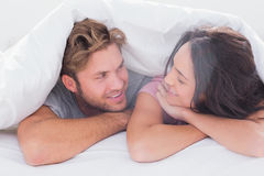 Couple under quilt smiling Royalty Free Stock Image