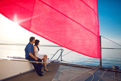 Couple under the red sail Stock Photography