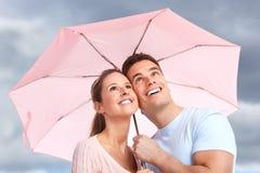 Couple under umbrella. Happy smiling couple under a pink umbrella Royalty Free Stock Image