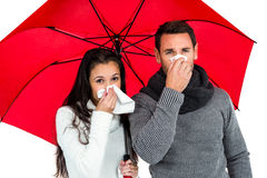 Couple under umbrella blowing their noses Stock Images