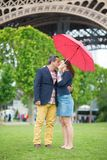 Couple under umbrella near the Eiffel tower Royalty Free Stock Images