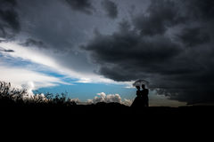 Couple under an umbrella in rain. Y stormy weather Royalty Free Stock Photography