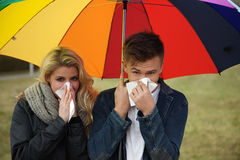 Couple under an umbrella sneeze Stock Photo