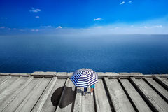 Couple under the umbrella standing on the roof on sea. Background Royalty Free Stock Photos