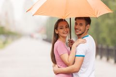 Couple under umbrella standing turned around. Royalty Free Stock Photos
