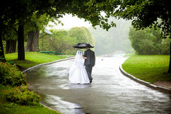 Couple under umbrella walking away on road Royalty Free Stock Photo