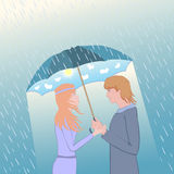 Couple under an umbrella. Woman and man looking at each other an enamored sight Stock Photography