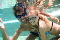 Couple under water in swimming pool Royalty Free Stock Images