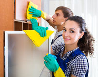 Couple in uniform cleaning indoors Stock Photo