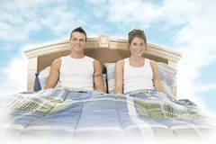 Couple unity. Young couple smile sitting in the bed next to each-other, with sky background stock images