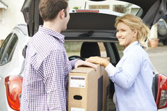 Couple Unloading New Television From Car Trunk Royalty Free Stock Images