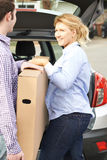 Couple Unloading New Television From Car Trunk Stock Images