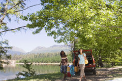 Couple unloading provisions from parked SUV on lakeside camping trip, smiling Stock Photos