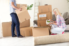 Couple unpack moving boxes. Royalty Free Stock Photography