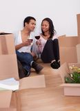 Couple Unpacking Boxes And Drinking Wine Stock Photo