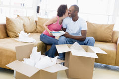 Couple unpacking boxes in new home kissing Royalty Free Stock Image