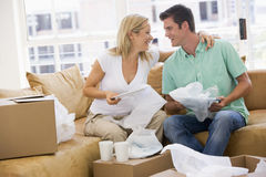 Couple unpacking boxes in new home smiling Stock Photos
