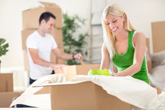Couple unpacking boxes Stock Photos