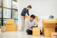 Couple unpacking cardboard boxes at new home. Moving house. Happy Young Couple unpacking cardboard boxes at new home. Moving house stock photos