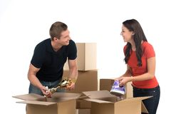 Couple unpacking cardboard boxes in new home. Royalty Free Stock Photos