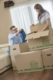 Couple unpacking cardboard boxes in new house Royalty Free Stock Photos