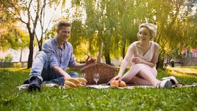 Couple unpacking fresh fruits from picnic basket, wonderful rest together Stock Image