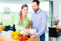 Couple unpacking grocery shopping bag at home Stock Photo
