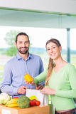 Couple unpacking grocery shopping bag at home Stock Image