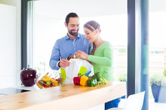 Couple unpacking grocery shopping bag at home Royalty Free Stock Images