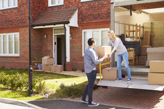Couple Unpacking Moving In Boxes From Removal Truck Stock Photos
