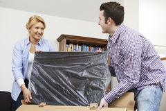 Couple Unpacking New Television At Home Royalty Free Stock Photos
