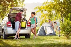 Couple unpacking things for camping trip. Couple unpacking things from the car for camping trip stock image