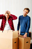 Couple unpaking boxes, woman looking to inside and aghast holding her head Royalty Free Stock Image