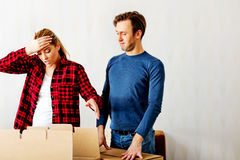 Couple unpaking boxes, woman looking to inside and aghast holding her head Stock Image