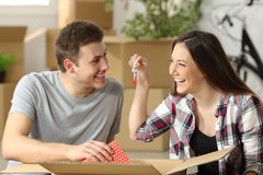Couple unpaking in their new house. Casual couple unpacking belongings and showing keys sitting on the floor of the loving room in their new house with boxes in Royalty Free Stock Images