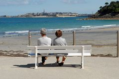 Couple on a bench facing Saint-Malo. Couple of unrecognizable backs sitting on a bench facing the sea in Brittany royalty free stock photography