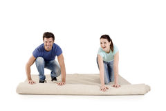 Couple unrolling a carpet. In the house Royalty Free Stock Photos