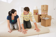 Couple Unrolling Carpet In New Home Stock Photo