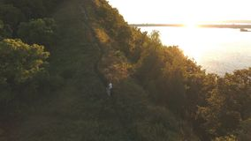 Couple up the hill, aerial shooting. Couple up the hill, aerial footage,shot with a camera, shooting from the height of bird flight stock video