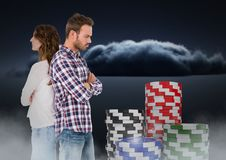 Couple upset back to back with gambling poker chips. Digital composite of Couple upset back to back with gambling poker chips Royalty Free Stock Photos